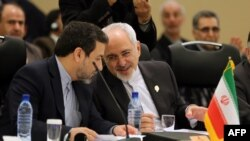 Iranian Foreign Minister Mohammad Javad Zarif (R) speaks to his deputy Abbas Araqchi during the opening session of a two-day ministerial conference of the Economic Cooperation Organisation (ECO), which groups 10 Asian and Eurasian countries, in Tehran on