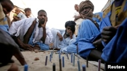 Men play a version of checkers using nuts and sticks placed in the sand at the Keube slum in Nouakchott March 13, 2007.
